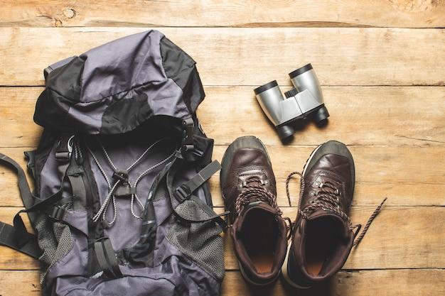 Ботинки для следа, рюкзак, бинокль, туристическое снаряжение на деревянном фоне. концепция походов, туризма, лагеря, горы, лес.