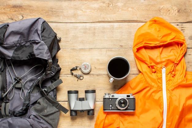 Рюкзак, бинокль, куртка, фотоаппарат и туристическое снаряжение на деревянном фоне. концепция походов, туризма, лагеря, горы, лес.