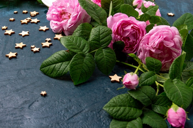 濃い青の表面にピンクのバラと星。コーヒーのコンセプト