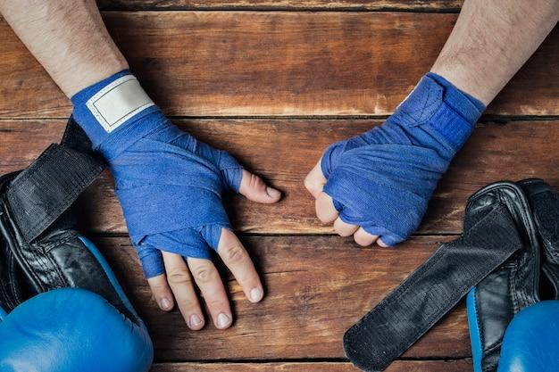 木製の背景とボクシングの試合前にテーピング中の男性の手。
