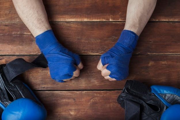 ボクシンググローブで木製の背景にテーピングボクシングの男性の拳。ボクシングトレーニングまたは戦いのためのトレーニングの概念。