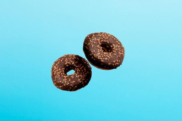 空を飛ぶドーナツとチョコレートのアイシングをブルーに。ベーカリー、ベーキングコンセプト。