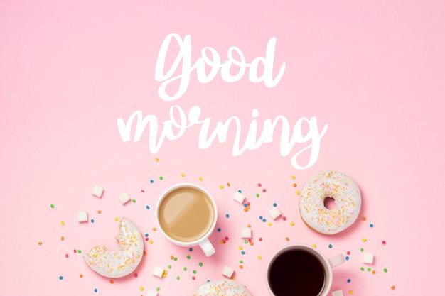 コーヒーまたは紅茶、ピンクの背景に新鮮なおいしい甘いドーナツとカップ。テキスト「おはよう」を追加しました。パン屋さんのコンセプト、焼きたてのペストリー、おいしい朝食、ファーストフード。フラット横たわっていた、トップビュー、コピースペース。