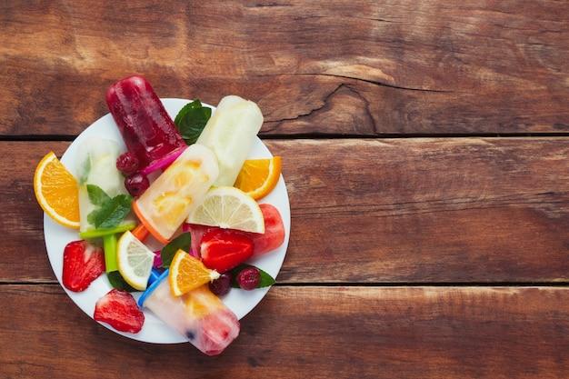 自家製のカラフルなフルーツアイスキャンデー、白い皿に新鮮な果物。