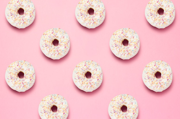 Свежие вкусные сладкие пончики на розовом фоне. концепция быстрого питания, пекарня, завтрак, сладости. минимализм. шаблон. плоская планировка, вид сверху.