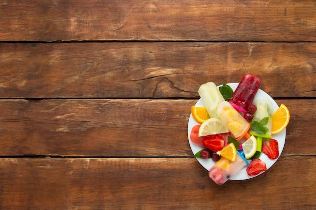 白い皿と木製の背景に新鮮な果物