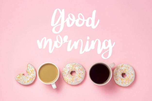 コーヒーまたは紅茶、ピンクの背景に新鮮なおいしい甘いドーナツとカップ。テキスト「おはよう」を追加しました。パン屋さんのコンセプト、焼きたてのペストリー、おいしい朝食、ファーストフード。