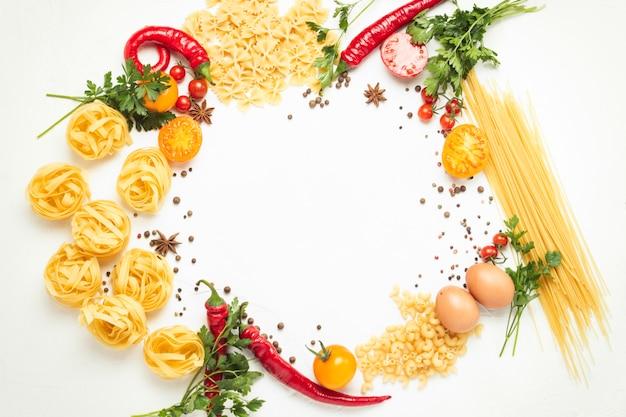 白い石の上にスパイス、赤唐辛子、卵、黄色と赤のトマトを使ったさまざまな種類のイタリアのパスタ。イタリア料理のパスタとソースを調理するコンセプト。