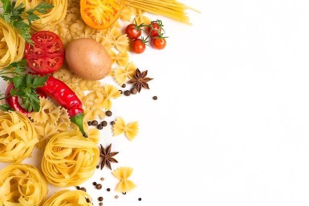 さまざまな種類のイタリアのパスタ、巣、スパゲッティ、スパイス、赤唐辛子、鶏の卵、トマト、チェリー、明るい白い石の背景。
