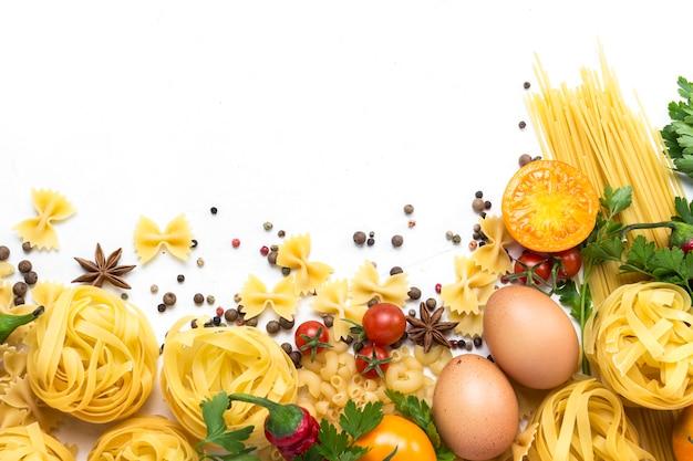 Итальянские макароны различных видов со специями, красный острый перец, куриные яйца на белом фоне.