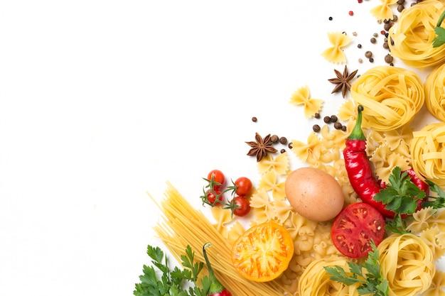 Итальянские макароны разных видов со специями, красный острый перец, куриные яйца, желтые и красные помидоры на белом фоне камня. концепция приготовления итальянской пасты и соуса.