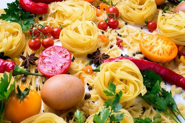 Итальянская паста разных видов со специями, красным острым перцем, куриными яйцами, желтыми и красными помидорами на белом