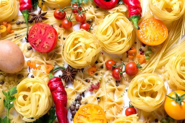 Итальянская паста различных видов со специями, красный острый перец, куриные яйца, желтые и красные помидоры на белом. концепция приготовления итальянской пасты и соуса