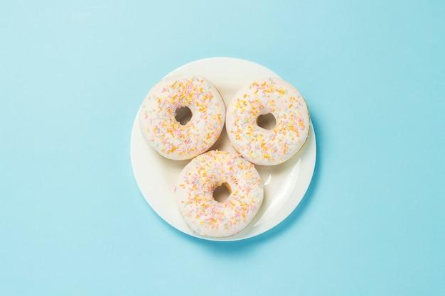 青色の背景に白いプレート上のドーナツ。ファーストフード、モーニングコーヒー、朝食の概念。