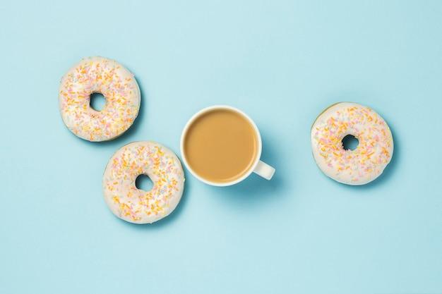 Белая чашка, кофе или чай с молоком и свежие вкусные пончики на синем фоне. концепция пекарня, свежая выпечка, вкусный завтрак, фаст-фуд.