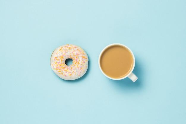Свежий вкусный сладкий пончик и чашка кофе или чая с молоком на синем фоне. концепция фаст-фуда, хлебопекарня, завтрак ,. минимализм.