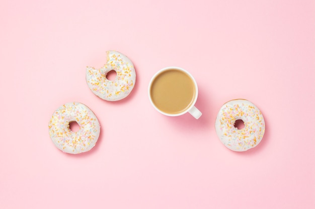ホワイトカップ、コーヒーまたは紅茶とミルクとピンクの背景に新鮮なおいしい甘いドーナツ。パン屋さんのコンセプト、焼きたてのペストリー、おいしい朝食、ファーストフード。