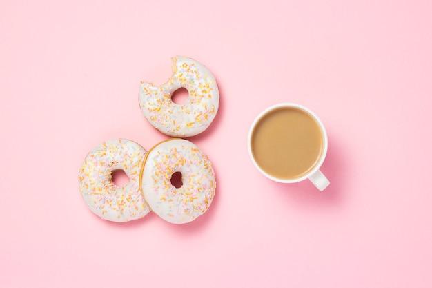 ホワイトカップ、コーヒーまたは紅茶とミルクとピンクの背景に新鮮なおいしい甘いドーナツ。パン屋さんのコンセプト、焼きたてのペストリー、おいしい朝食、ファーストフード。フラット横たわっていた、トップビュー。