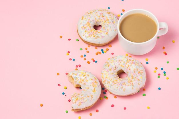 Чашка кофе с молоком, свежие вкусные сладкие пончики на розовом фоне. концепция быстрого питания, пекарня, завтрак, сладости. минимализм. плоская планировка, вид сверху, копия пространства.
