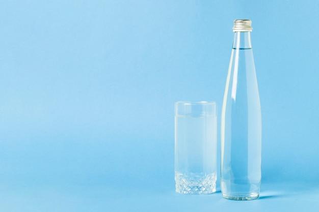 Стеклянная бутылка и стакан с кристально чистой освежающей водой на синей поверхности. концепция красоты и здоровья, водный баланс, жажда, лето