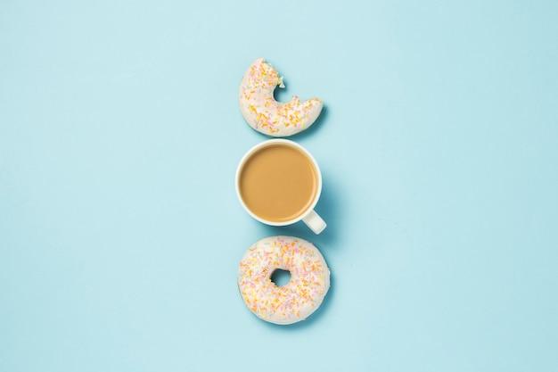白いカップ、コーヒーまたは紅茶とミルクと青色の背景に新鮮なおいしいドーナツ。パン屋さんのコンセプト、焼きたてのペストリー、おいしい朝食、ファーストフード。フラット横たわっていた、トップビュー。