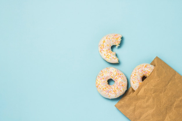 Бумажный пакет и свежие вкусные сладкие пончики на синем фоне. концепция фаст-фуд, пекарня, завтрак, сладости. минимализм. плоская планировка, вид сверху.