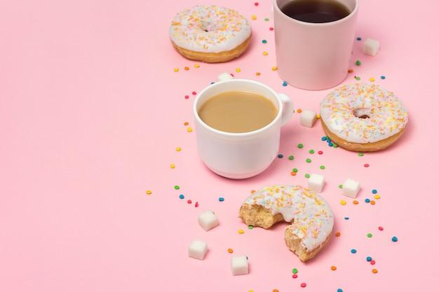 Чашки с кофе или чаем, свежие вкусные сладкие пончики на розовом фоне. концепция быстрого питания, пекарня, завтрак, сладости, кафе. плоская планировка, вид сверху, копия пространства.