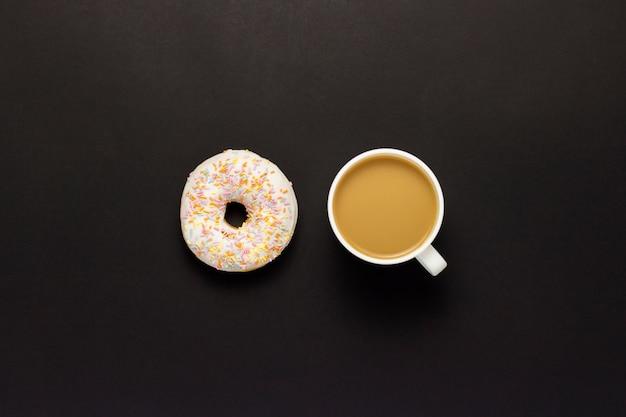おいしい、甘い、新鮮なドーナツ、一杯のコーヒー、黒の背景。朝食、ファーストフード、コーヒーショップ、ベーカリーの概念。ミニマリズム。フラット横たわっていた、トップビュー。