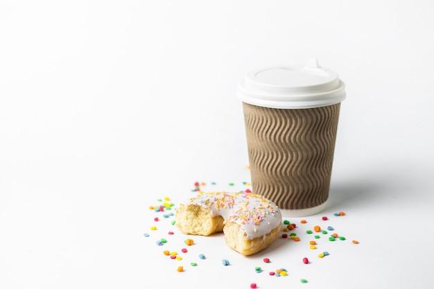 蓋、コーヒーまたは紅茶と新鮮なおいしいドーナツと白い背景の甘い色とりどりの装飾的なキャンディーと紙コップ。パン屋さんのコンセプト、焼きたてのペストリー、おいしい朝食、ファーストフード。