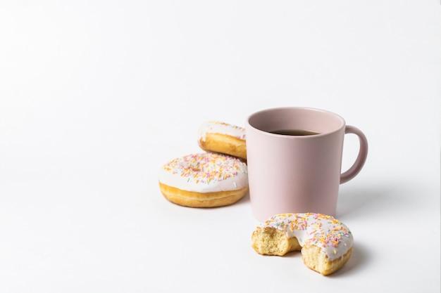 コーヒーまたは紅茶と新鮮なおいしいドーナツ、白地に甘い色とりどりの装飾的なキャンディーとピンクのカップ。パン屋さんのコンセプト、焼きたてのペストリー、おいしい朝食、ファーストフード。