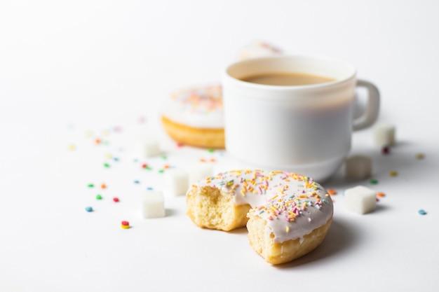 ホワイトカップ、コーヒーまたは紅茶とミルクと新鮮なおいしいドーナツ、白い背景に甘い色とりどりの装飾的なキャンディ。パン屋さんのコンセプト、焼きたてのペストリー、おいしい朝食、ファーストフード。