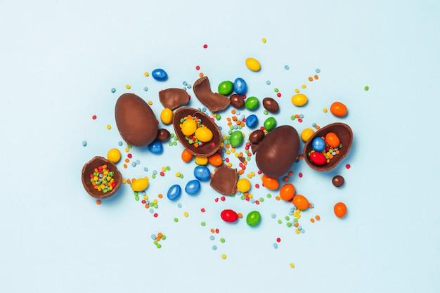 壊れたとチョコレート全体のイースターエッグ、青の背景に色とりどりのお菓子。イースターを祝う概念、イースター装飾、イースターバニーのお菓子を検索します。フラット横たわっていた、トップビュー。コピースペース。
