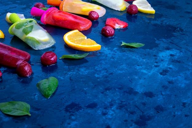Самодельный яркий фруктовый эскимо со вкусом клубники, вишни, лимона, апельсина, лимона и мяты и свежих фруктов для мороженого на темно-синем