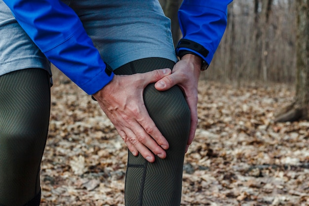 トレーニング服の男は、屋外トレーニングでジョギング中に膝の怪我をした。スポーツ傷害、ランニングテクニック、間違ったランニング、腱炎、大きな負荷の概念。