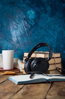 本が積み上げられ、ヘッドフォン、ホワイトカップ、木製の日記を開きます。オーディオブックの概念