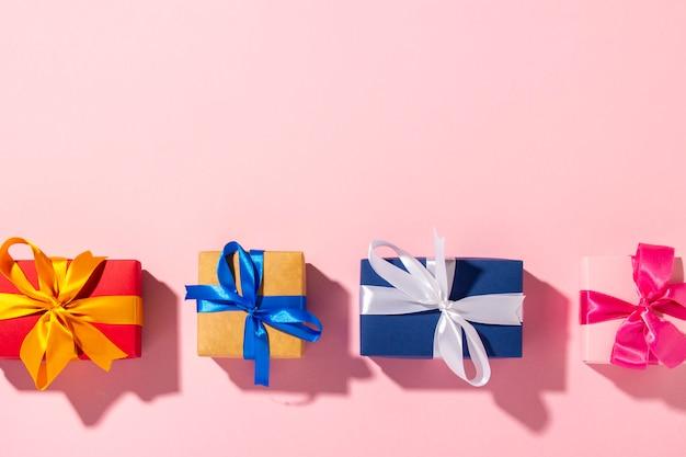 Подарки с лентой на розовом фоне при естественном освещении. современное. праздник, семья, любимая, для него. баннер. плоская планировка, вид сверху