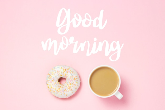 コーヒーまたは紅茶のカップ、ピンクの新鮮なおいしい甘いドーナツ。テキスト「おはよう」を追加しました。パン屋さんのコンセプト、焼きたてのペストリー、おいしい朝食、ファーストフード、コーヒーショップ。フラット横たわっていた、トップビュー。