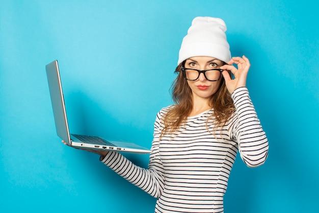 ノートパソコンと白い帽子の深刻な少女は、青のメガネの下から見える
