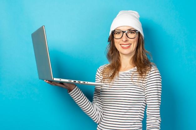 ラップトップ、メガネの女の子、青の白い帽子を保持している若い女の子の笑顔