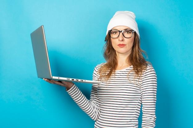 青のラップトップで白い帽子の深刻な少女
