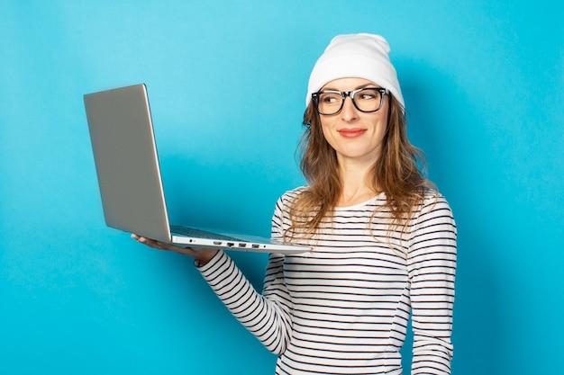 笑みを浮かべて少女は青いノートパソコンで見える