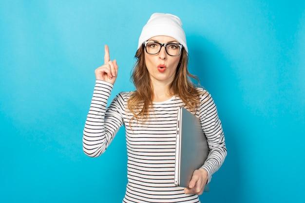 メガネと白い帽子のショックを受けた少女、ラップトップを保持し、青に指を上向き