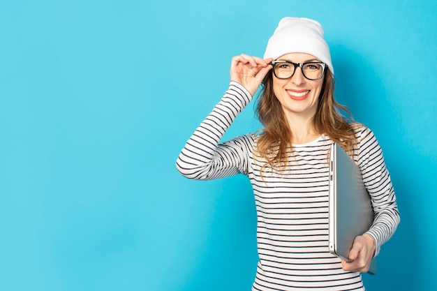 ラップトップを白い帽子の少女の笑顔を青のメガネにしがみつく
