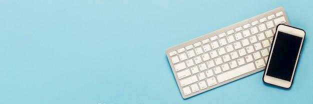 青色の背景にキーボードと白の携帯電話。