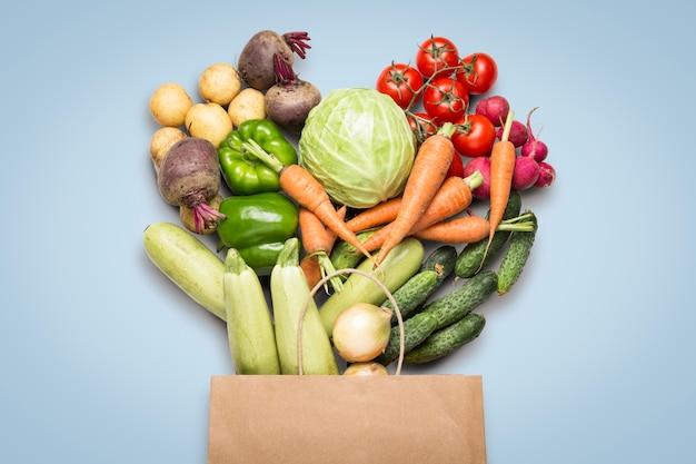 紙の買い物袋と青い表面に新鮮な有機野菜。農場野菜の購入、健康管理、菜食主義の概念。カントリースタイル、ファームフェア。フラット横たわっていた、トップビュー