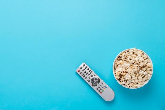 Чаша с попкорном и пультом для телевизора на синем фоне. концепция домашнего кинотеатра, кино, досуг. плоская планировка, вид сверху