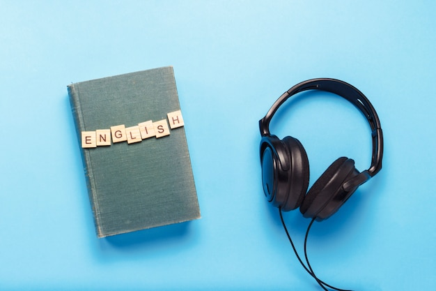 青い背景にテキストの英語と黒いヘッドフォンが付いた青いカバーが付いている本。オーディオブック、独学、独立した英語学習のコンセプト。フラット横たわっていた、トップビュー