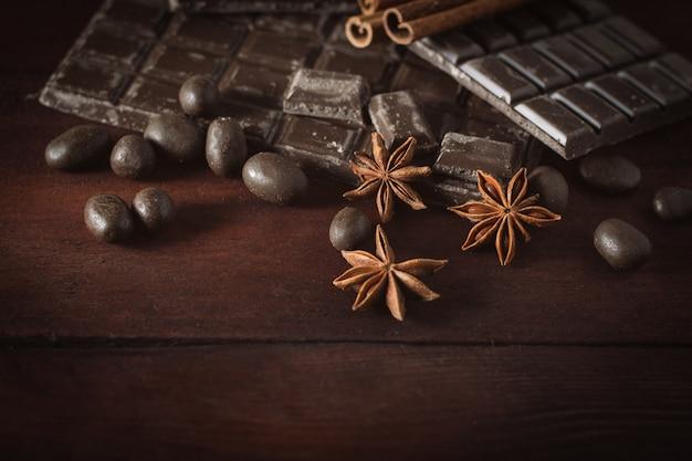 暗い木製の表面にチョコレート、シナモン、チョコレートボール。コピースペース