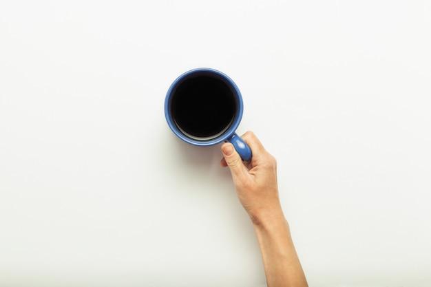 青色の背景にホットコーヒーとカップを持っている手。コーヒーまたは紅茶の朝食のコンセプトです。おはよう、夜、不眠症。フラット横たわっていた、トップビュー