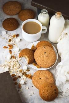 オートミールクッキー、書籍、オートミールフレーク、ミルク入りコーヒー、軽い表面のレーズン。おはようと朝食のコンセプト